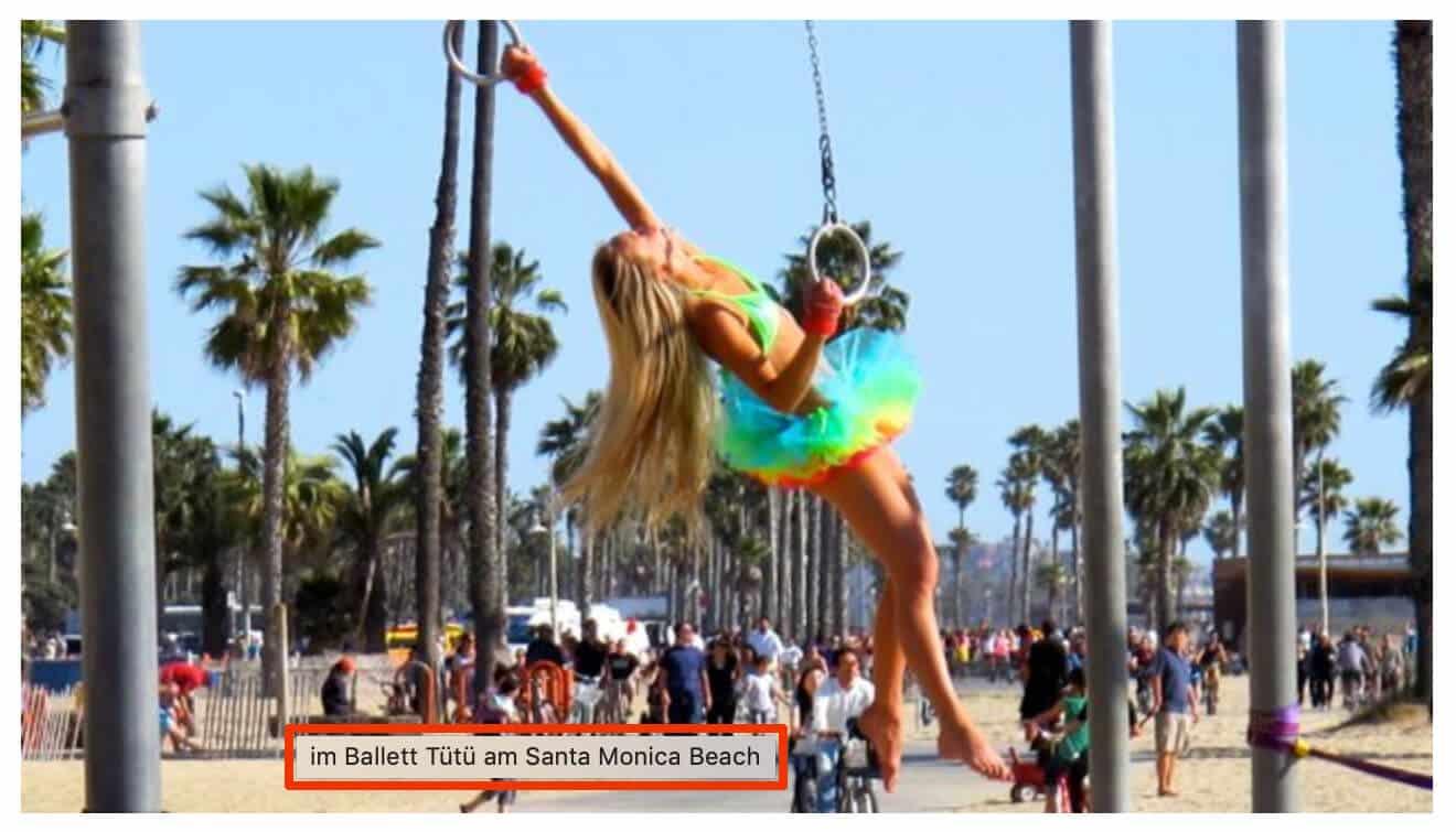 Frau hängt im bunten Ballett-Tutu an Ringen am Muscle Beach